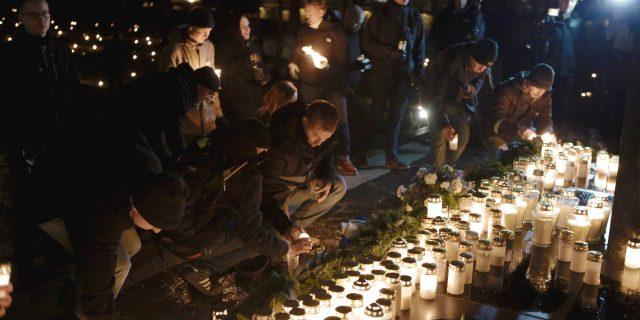 LKS 20141206  Kansallinen vastarinta KVR:n 612-soihtukulkueen osallistuja sytyttämässä kynttilöitä sankarihaudalle saavuttuaan Hietaniemen hautausmaalle Helsingissä 6. joulukuuta 2014.    LEHTIKUVA / SEPPO SAMULI